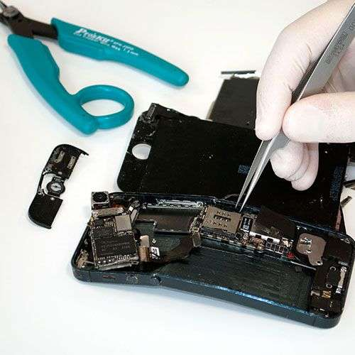 Close up of a broken iPhone having parts extracted by a technician